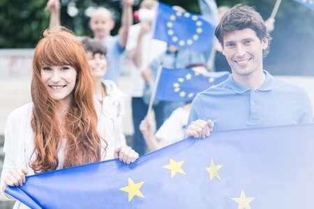 Beeld van jonge gemeenschap werknemers met europese unie vlaggen Stockfoto