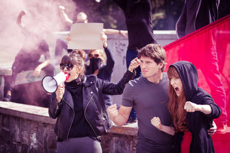 demonstrator: Photo of woman with megaphone and protesting couple