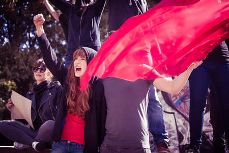 man power: Picture of young active demonstrators with red flag Stock Photo