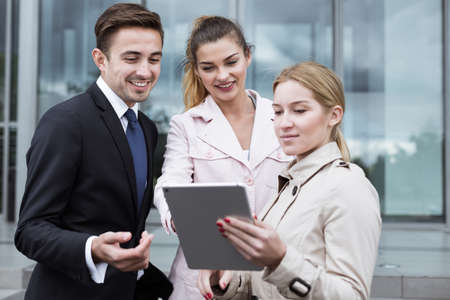 personas leyendo: Empleados Corporación que usa la tableta en la calle