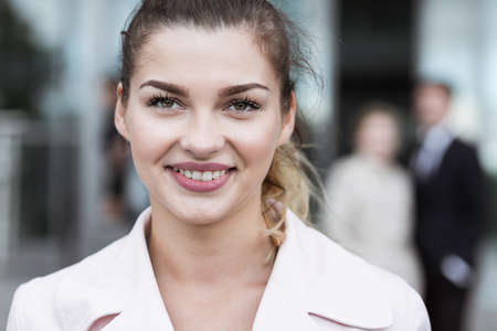 newcomer: Young woman is smiling outside corporate office Stock Photo
