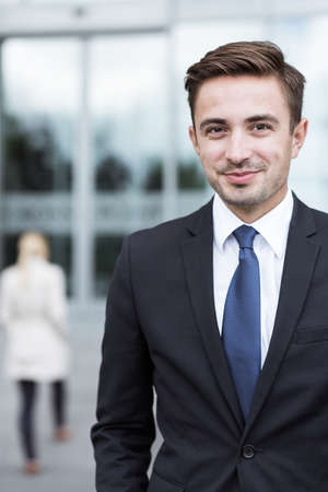 smiling businessman: Portrait of young confident businessman outside office