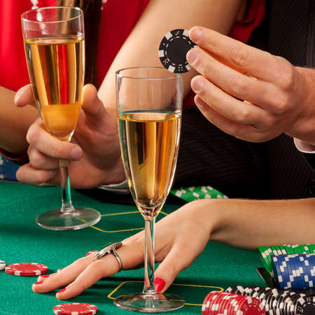 gamblers: Gamblers holding casino chips and glasses of champagne Stock Photo