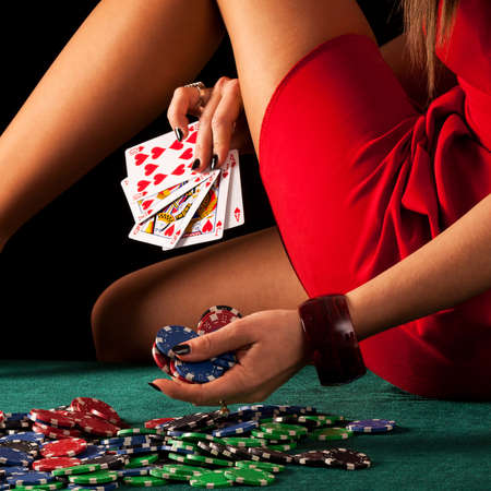 Een sexy gokken vrouw met een poker royal flush