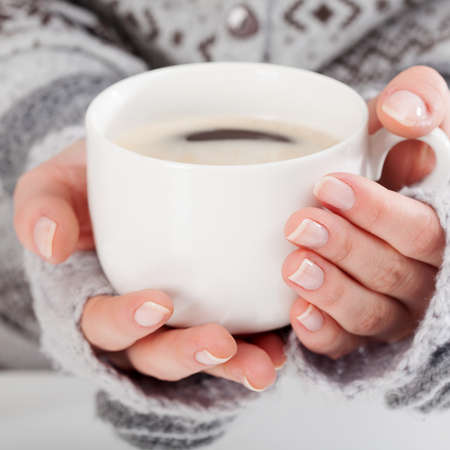 guantes: Primer plano de la mano de una mujer que sostiene una taza de café caliente Foto de archivo