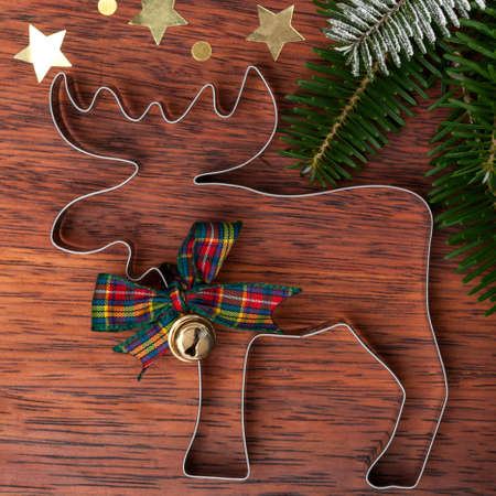 cookie cutter: Reindeer cookie cutter on a wooden background, view from above