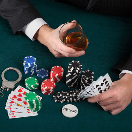 gambler: Gambler holding a glass of alcohol and handcuffs
