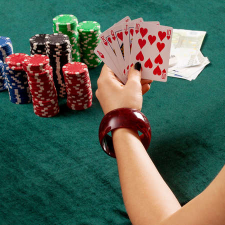 poker player: A poker player holding a stright flush of hearts Stock Photo