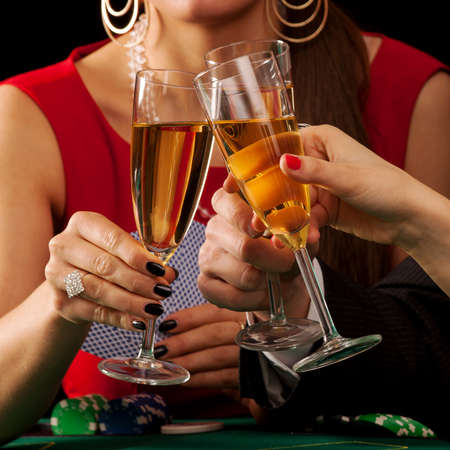 proposing a toast: Gamblers drinking a glass of champagne by a table Stock Photo