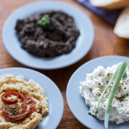 pastes: Three tasty pastes of hummus, tapenade and cottage cheese Stock Photo