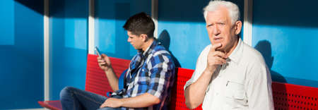 man confused: Older confused man and young boy on a bus stop