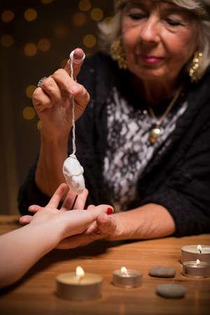 foretell: Close-up of fortune teller using magic pendulum