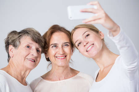 Smiling granddaughter taking perfect family selfie - horizontal view
