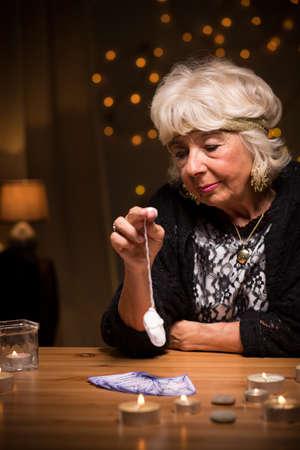 foretelling: Female fortune teller predicting future with pendulum Stock Photo