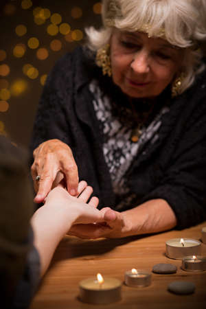 palmistry: Elder magic woman foretelling future from hand