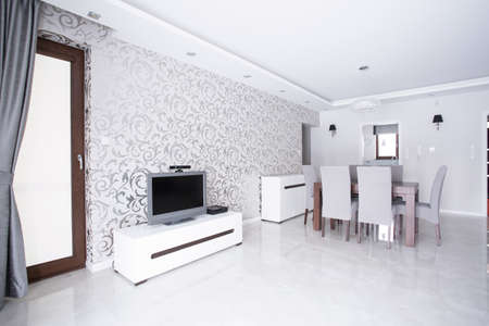Contemporary spacious white living room with patterned wallpaper
