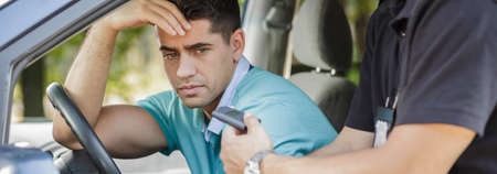 sobriety: Policeman wants male driver to take breatha test Stock Photo