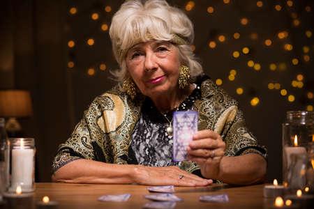 foretell: Elder female tarot reader holding magic card
