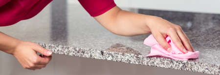 clout: Closeup of young woman cleaning granite countertop Stock Photo