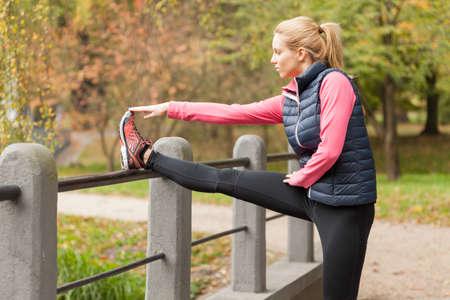 若い女の子が公園でジョギングする前にストレッチします。 写真素材