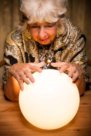 Female seer forecasting future from crystal ball Stock Photo