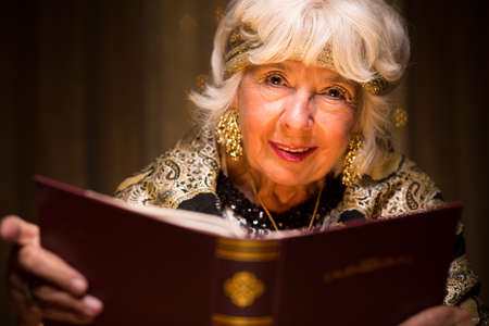 mystique: Elder female fortune teller holding magic book