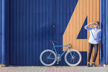 somebody: Businessman standing beside his bicycle and waiting for somebody