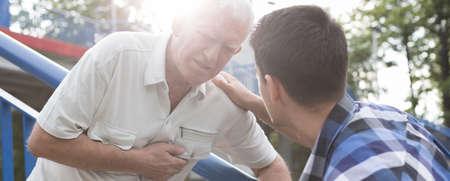 persona mayor: Hombre joven que cuida que ayudar al hombre viejo y enfermo en una calle