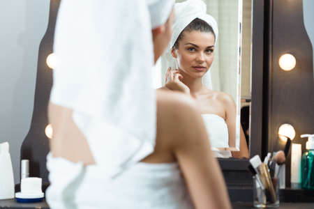 light complexion: Image of pretty female looking in the mirror