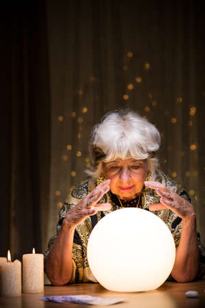 Donna magica raccontando futuro da sfera di cristallo Archivio Fotografico - 47016384