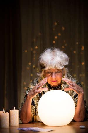 Magic vrouw vertelt toekomst van kristallen bol Stockfoto