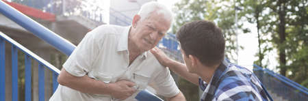 senility: Elderly man with heart attack and helpful young man