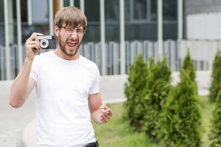 hombres guapos: Hombre joven feliz que sostiene la c�mara y apuntando Foto de archivo
