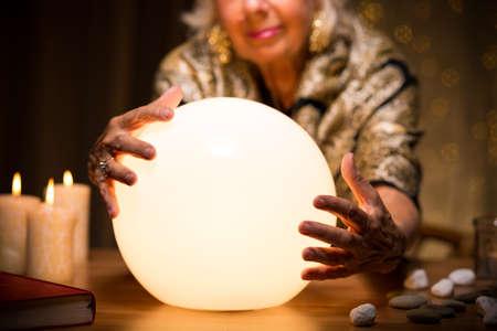 adivino: Primer plano de una mujer de magia con bola de cristal