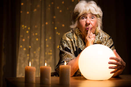adivino: Mujer que ve la adivinaci�n de bola m�gica Foto de archivo