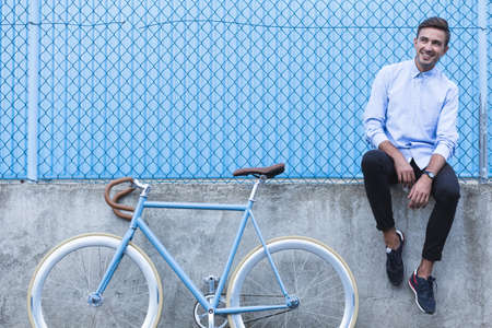parapet wall: Horizontal view of handsome businessman with bike