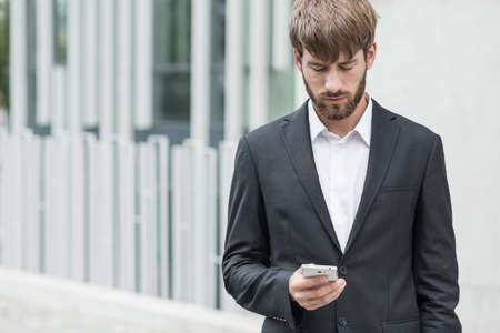 coaches: Young businessman is writing email on smartphone