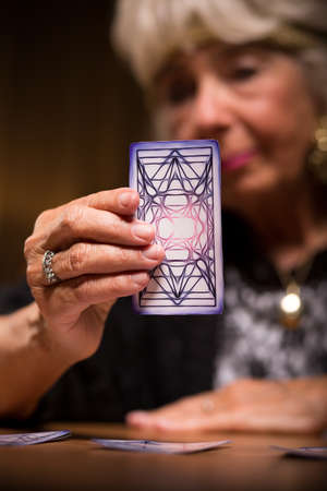 Elder female tarot reader holding magic card