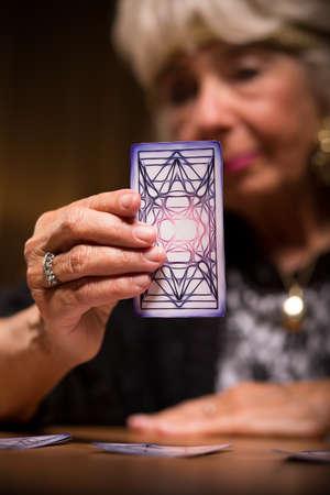 Oudere vrouwelijke tarot lezer die magische kaart Stockfoto