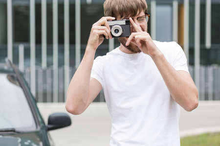 young boy smiling: Young man in white shirt is taking photo Stock Photo