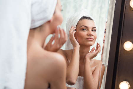 Image of a beautiful content woman pampering her skin