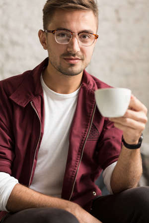 young boy smiling: Young smart hipster boy drinking hot coffee