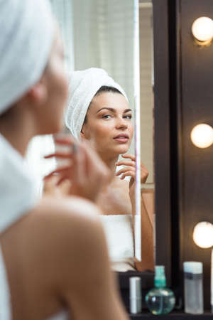 at the mirror: Image of a confident woman admiring herself
