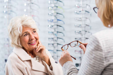 optical: Young optician selling glasses in optical shop Stock Photo