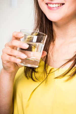 tomando agua: Primer plano de la mujer que bebe el agua clara sana