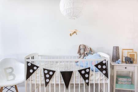 Beeld van witte babybedje met decoratie