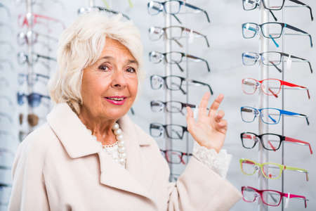shortsightedness: Senior woman choosing eyeglasses in optician store