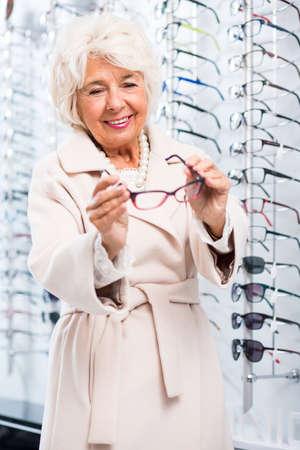 specs: Senior woman choosing spectacles in optical shop