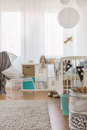 Photo of cosy toddler bedroom with crib and cabinet