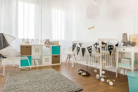 école maternelle: Image de la spacieuse chambre de bébé avec des meubles blancs